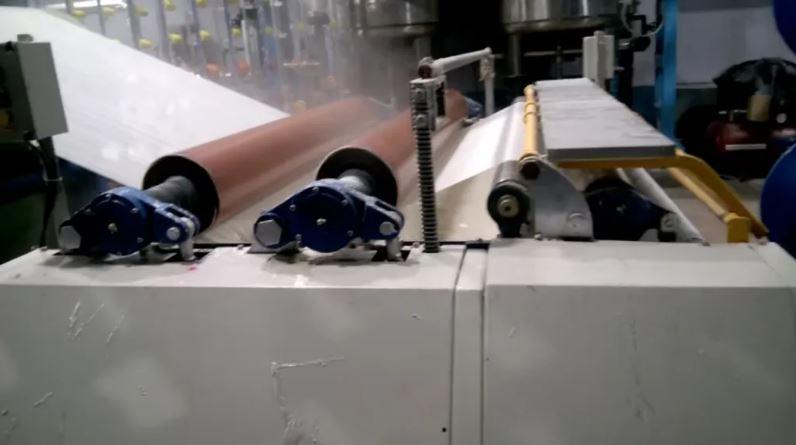 Cận cảnh một chiếc máy hồ sợi đang thực hiện quá trình hồ sợi vải