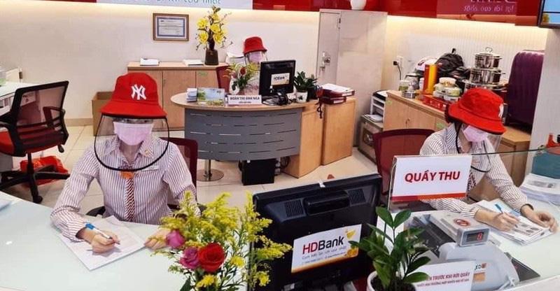 Giao dịch viên của ngân hàng HD bank đang sử dụng mũ chống giọt bắn & khẫu trang để phòng tránh dịch bệnh trong quá trình làm việc